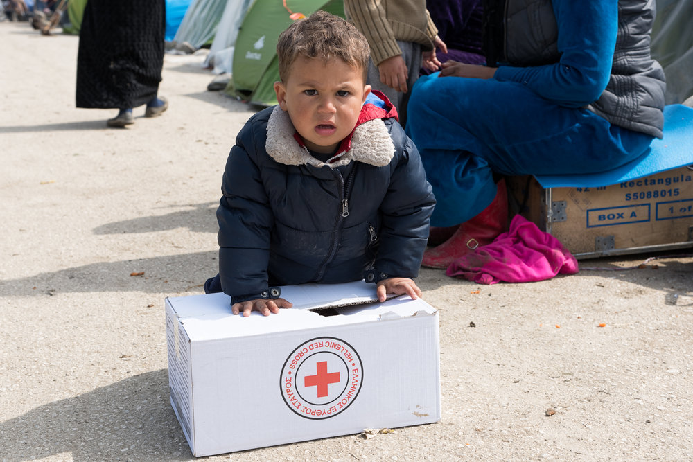 A little boy tries to carry a box with supplies given from the Greek Red Cross on March 17, 2015 in the refugees camp of Eidomeni.